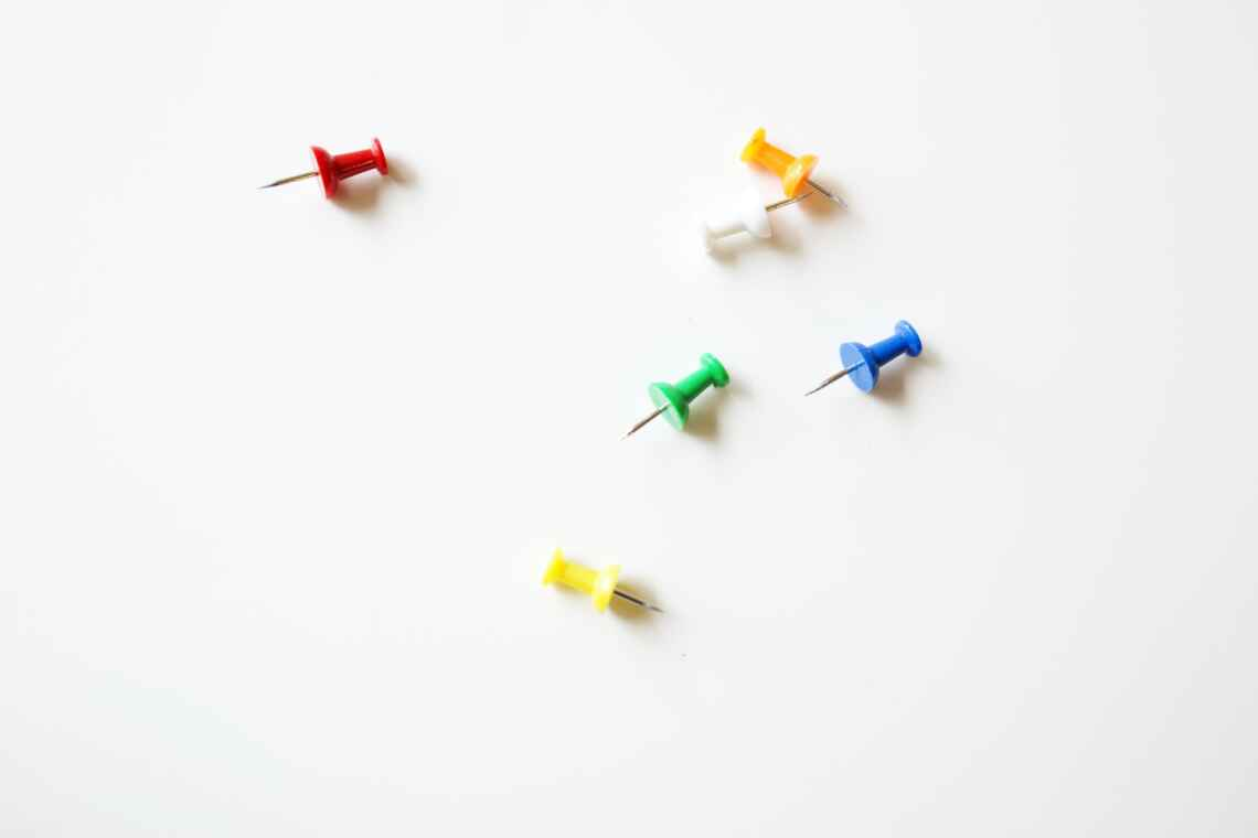 Bright colored pushpins on a white table